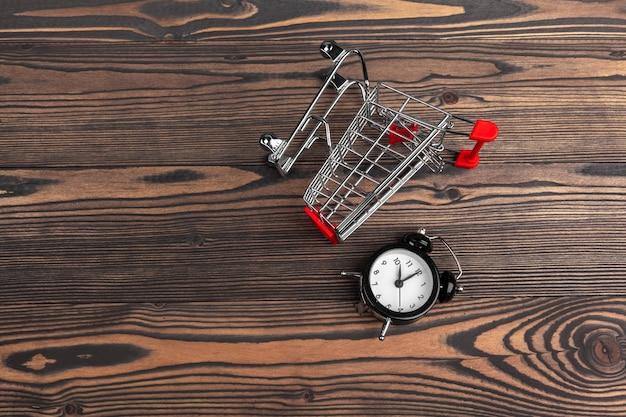 Grande despertador no carrinho de compras em uma mesa