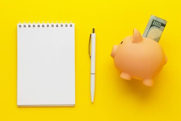 Grande dinheiro rosa fofo com 100 dólares e bloco de notas em branco com caneta