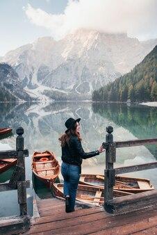 Grande distância. nevoeiro no topo das colinas. mulher de chapéu preto, apreciando a paisagem majestosa da montanha perto do lago com barcos