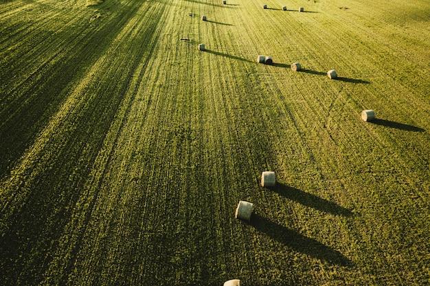 Grande e belo campo agrícola com pilhas de feno, tiro de cima