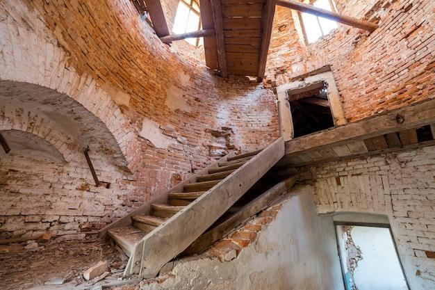 Grande e espaçosa sala de porão vazia abandonada do edifício antigo ou palácio com paredes de tijolo rebocadas, pequenas janelas, piso sujo e escada de madeira.