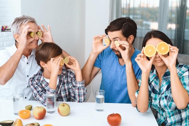 Grande e feliz família cobre os olhos com frutas.