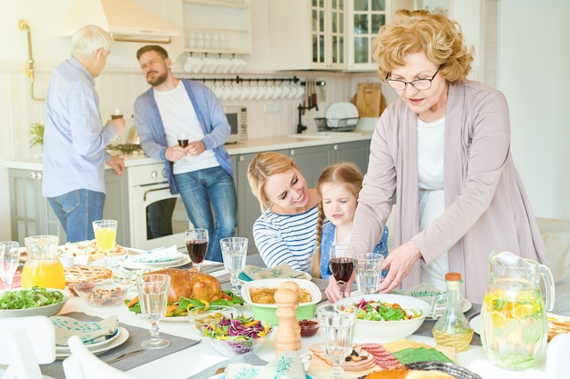 Grande e feliz família preparando a mesa de jantar para festa