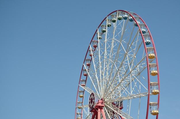 Grande e moderna roda-gigante multicor no céu azul limpo