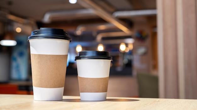 Grande e pequena xícara de café em uma mesa de madeira em um café. ideia de reciclagem