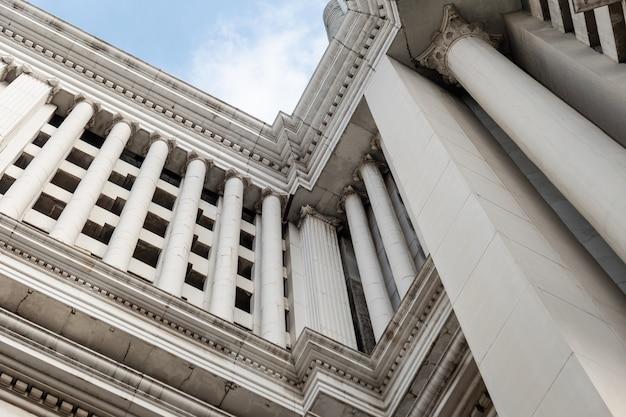 Grande edifício arquitetônico de estilo romano antigo com pilares e céu azul