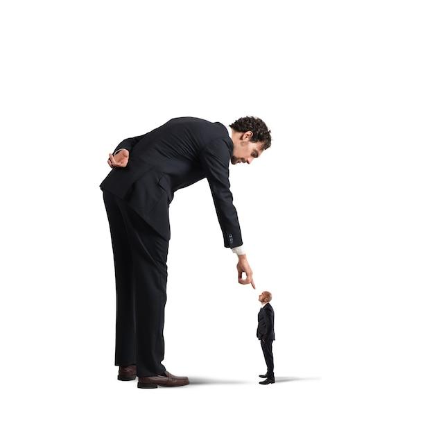Grande empresário olhando e apontando para um homem pequeno