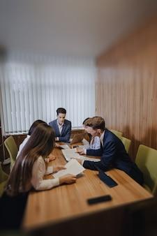 Grande equipe de pessoas está trabalhando em uma mesa para laptops, tablets e papéis, no fundo uma grande tv na parede de madeira