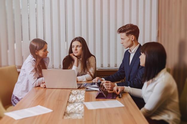 Grande equipe de pessoas está trabalhando em uma mesa para laptops, tablets e papéis