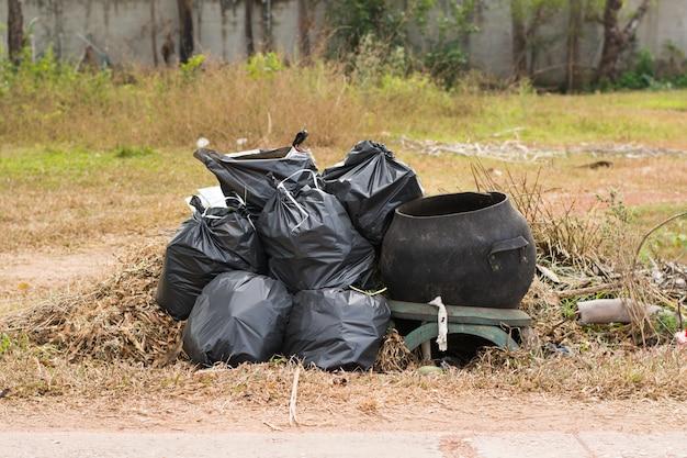 Grande escaninho verde do wheelie para desperdícios, fundo público do lixo, pilha grande do lixo e waiste em sacos pretos.