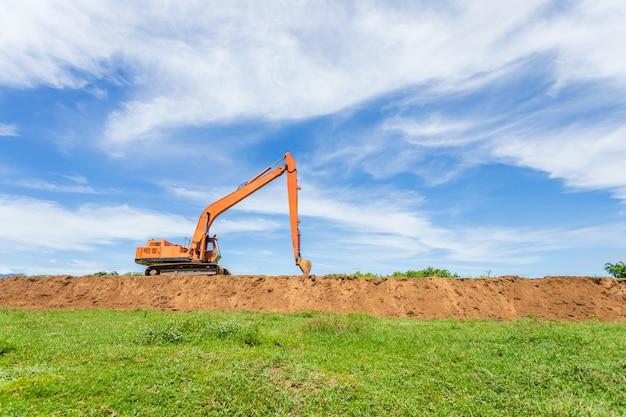 Grande escavadeira de esteiras laranja opera e escavando o solo no local