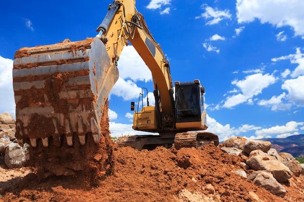 Grande escavadeira despejando uma colher de sujeira