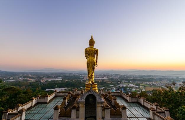 Grande estátua de buda dourado em wat phra that kao noi na manhã da província de nan, tailândia