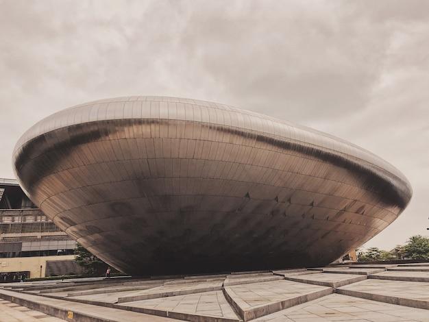 Grande estrutura metálica no meio de uma cidade moderna