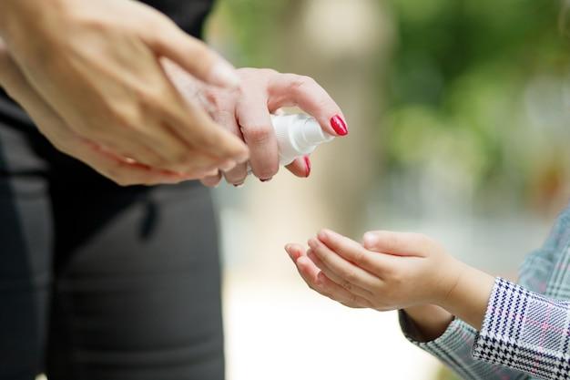 Grande família aplicando desinfetante para as mãos para limpar e desinfetar as mãos ao ar livre. mulher aplicando spray