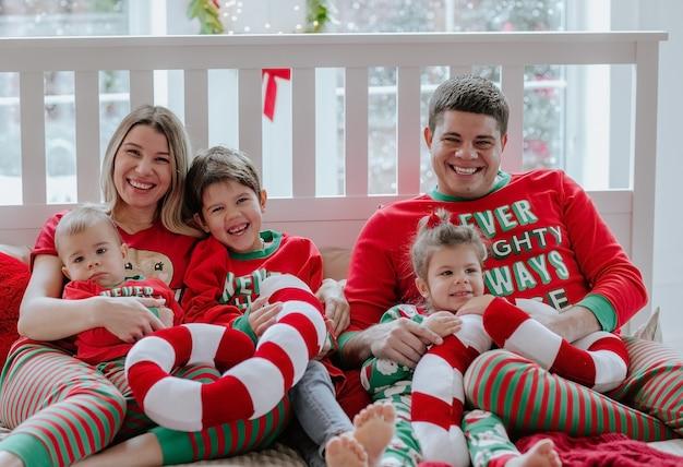 Grande família de cinco pessoas com pijama de natal, sentados juntos na cama branca contra uma grande janela com configuração de neve.