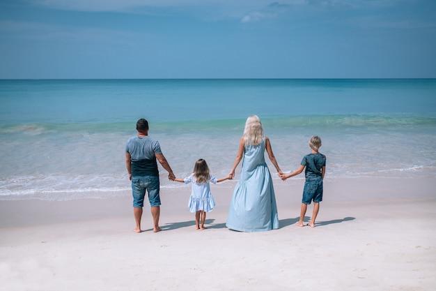 Grande família de mãos dadas e em pé perto do mar