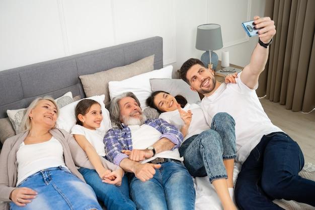 Grande família multigeracional, pai, mãe e avós sênior com uma menina tirando uma selfie