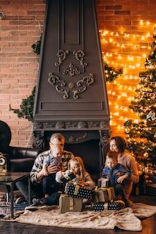 Grande família na véspera de natal com presentes pela árvore de natal