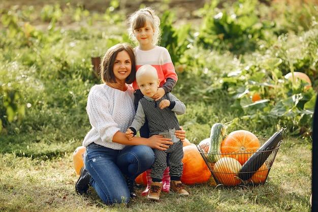 Grande família sentada em um jardim perto de muitas abóboras