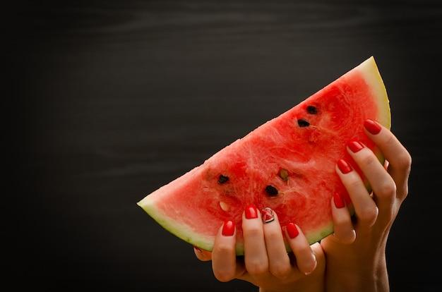 Grande fatia de melancia nas mãos femininas em um espaço preto, para texto