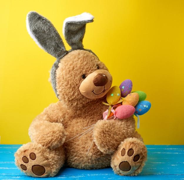 Grande fofo urso de pelúcia marrom segurando ovos de páscoa coloridos, vestindo uma máscara de coelho com orelhas compridas na cabeça