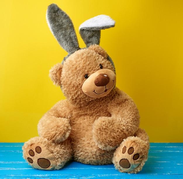 Grande fofo urso de pelúcia marrom, vestindo uma máscara de coelho com orelhas compridas na cabeça