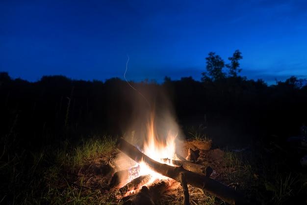 Grande fogo laranja na fogueira ao pôr do sol com céu azul escuro