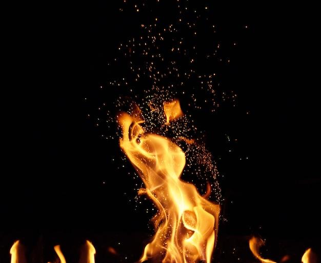 Grande fogueira acesa com chamas e faíscas laranja