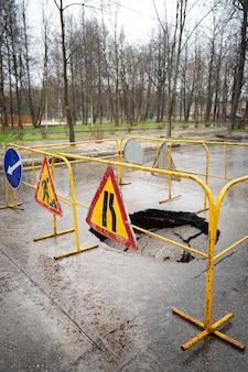Grande fosso na estrada após chuvas fortes e afundamento com uma cerca e placas de aviso