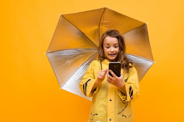 Grande foto colorida de uma menina com capa de chuva e um guarda-chuva aberto com um telefone nas mãos dela sobre um fundo amarelo