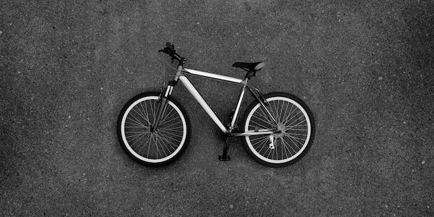Grande foto super da bicicleta que encontra-se no pavimento.