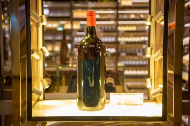 Grande garrafa de vinho em uma vitrine brilhante.