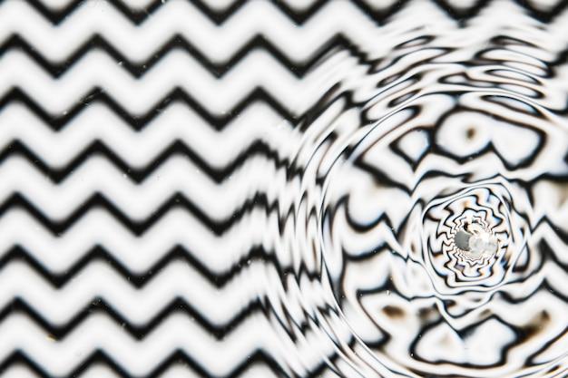 Grande gota de água em uma superfície de piscina preto e branco