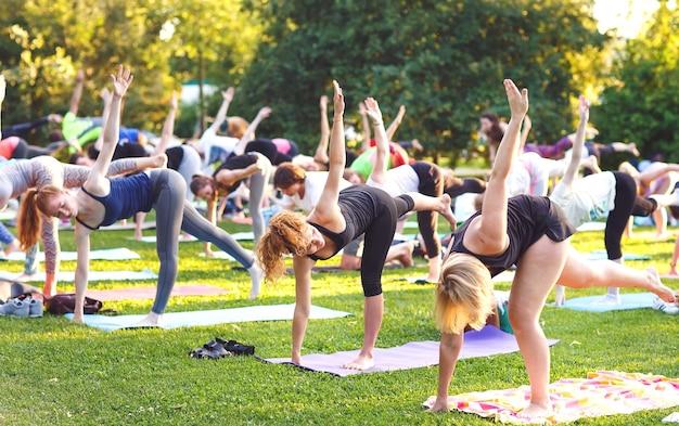 Grande grupo de adultos em aula de ioga ao ar livre no parque