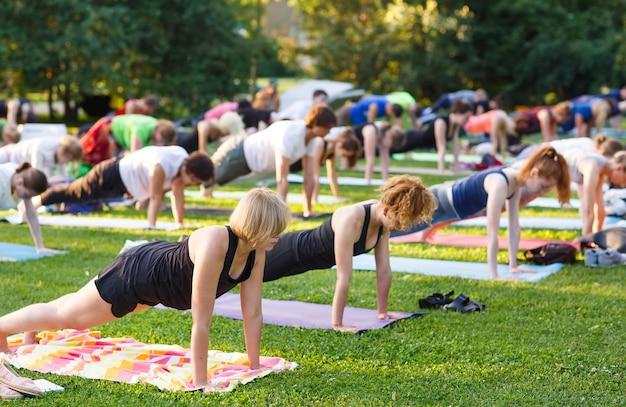 Grande grupo de adultos que frequentam uma aula de ioga fora no parque