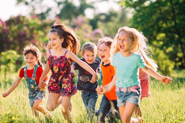 Grande grupo de crianças, amigos meninos e meninas correndo no parque no dia de verão ensolarado em roupas casuais.