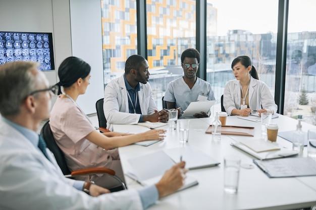 Grande grupo de médicos discutindo o caso enquanto está sentado na mesa de reunião durante a conferência médica, copie o espaço