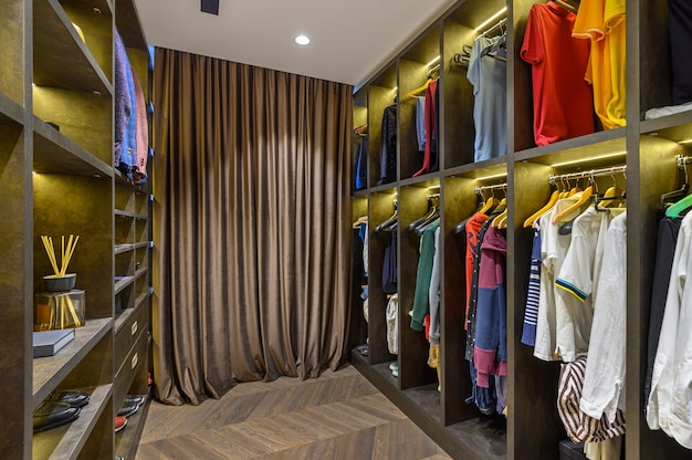 Grande guarda-roupa masculino de luxo com diversos sapatos e acessórios, vista frontal