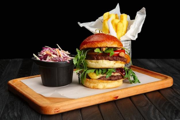Grande hambúrguer com batatas fritas e salada de repolho