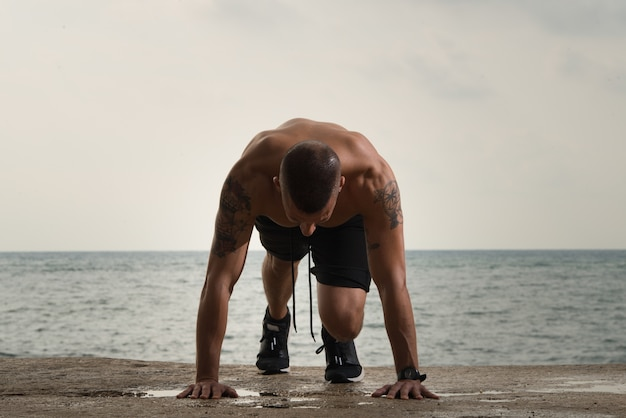 Grande homem musculoso fazendo flexões no chão