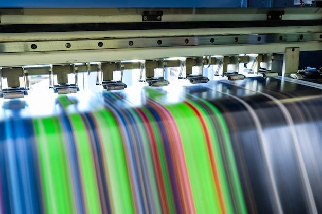 Grande impressora a jato de tinta multicolor trabalhando em banner de vinil