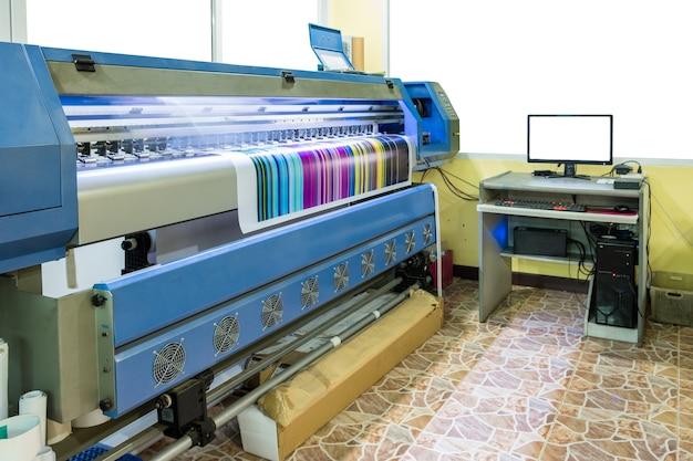 Grande impressora jato de tinta multicolor cmyk trabalhando em banner de vinil com controle de computador