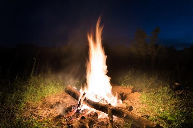 Grande incêndio na fogueira laranja ao pôr do sol com céu azul escuro à noite