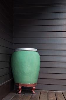 Grande jarra de água verde feita à mão em cerâmica no fundo de madeira da parede, jarra de cerâmica verde com água antiga e maravilhosa jarra