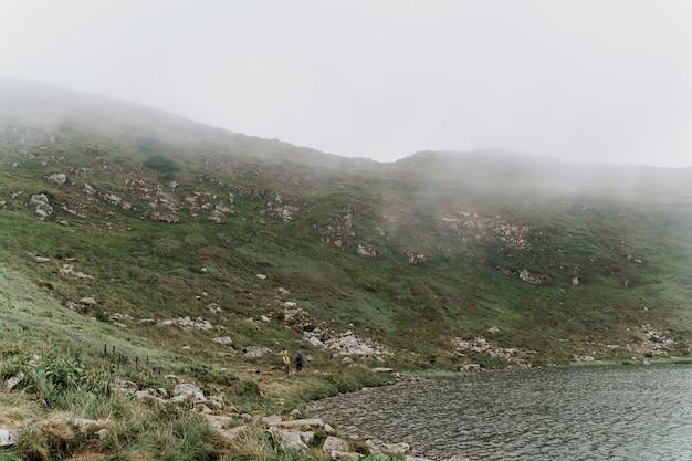 Grande lago e rochas em dia de nevoeiro