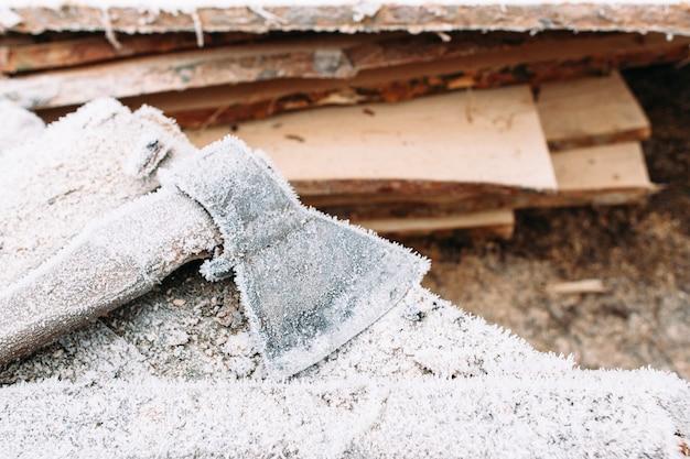 Grande machado do lado de fora perto de um monte de lenha. geada eclodiu no quintal. ferramentas externas deixadas no inverno. frio, geadas precoces, conceito rouco