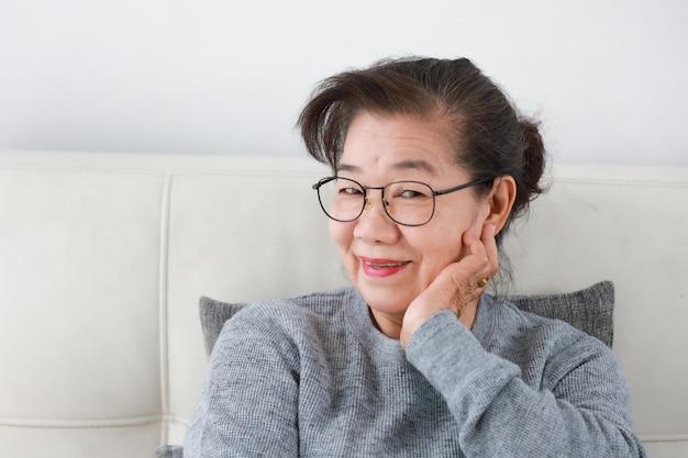 Grande mãe asiática sênior na sala de estar feliz rosto