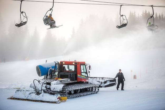 Grande máquina de limpeza de neve trabalhando em uma pista de esqui sob cadeiras de cabos