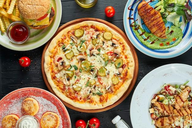 Grande mesa de jantar com vários alimentos - frango grelhado, pizza, salada caesar, hambúrguer e cheesecakes